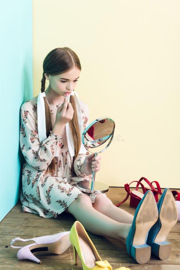 fille attirante de la jeunesse appliquant le rouge à lèvres avec le miroir tout en se reposant sur le plancher images libres de droits