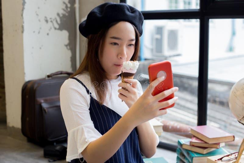 Fille attirante et élégante asiatique mangeant la crème glacée et prenant un tir de photo de selfie images libres de droits