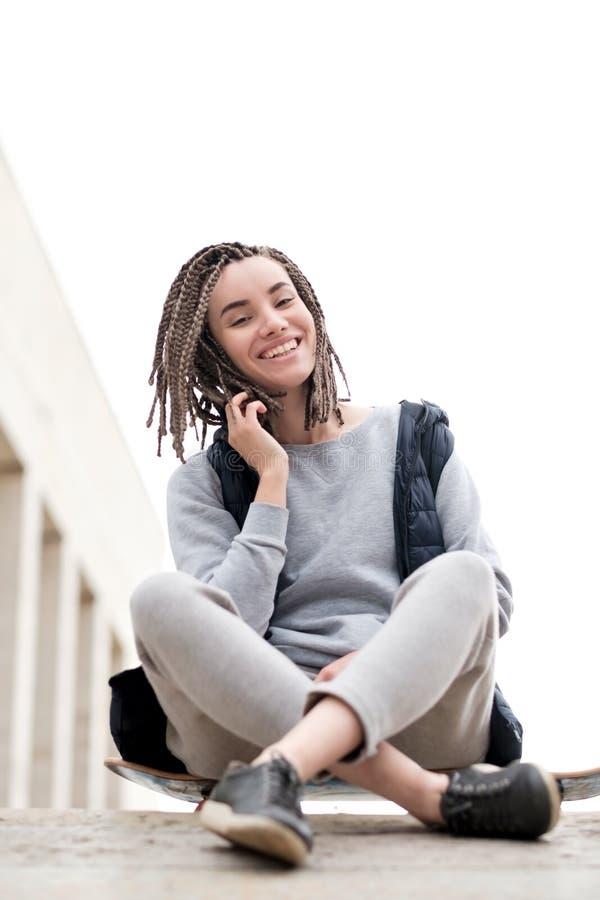 Fille attirante et souriante d'adolescent détendant avec une planche à roulettes et s'asseyant, parlant à quelqu'un au téléphone photographie stock