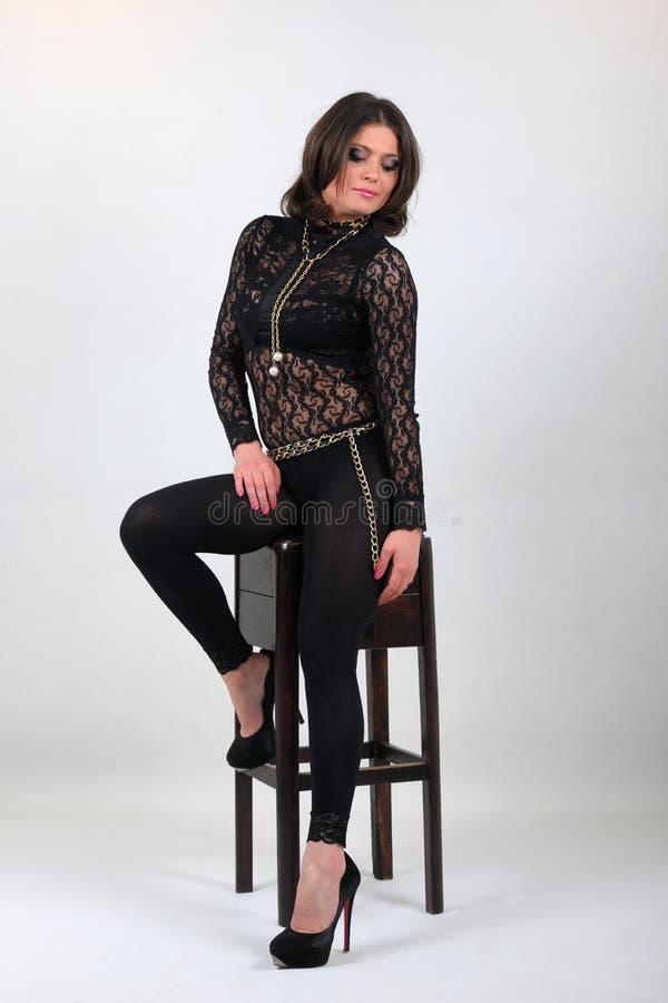 Fille attirante, magnifique et jolie s'asseyant sur un tabouret de bar et une pose photos stock