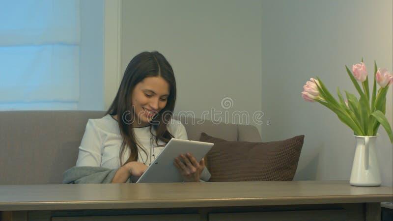 Fille attirante s'asseyant sur le sofa utilisant le touchpad et le sourire image libre de droits