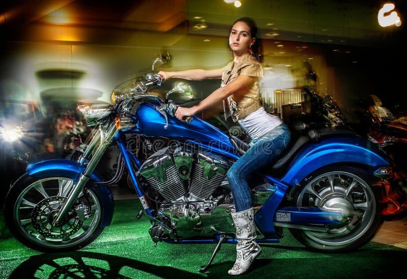 Fille attirante s'asseyant sur une moto bleue, exposition de moto photo stock