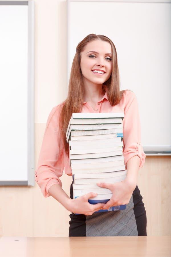 Fille attirante tenant la pile des livres photographie stock