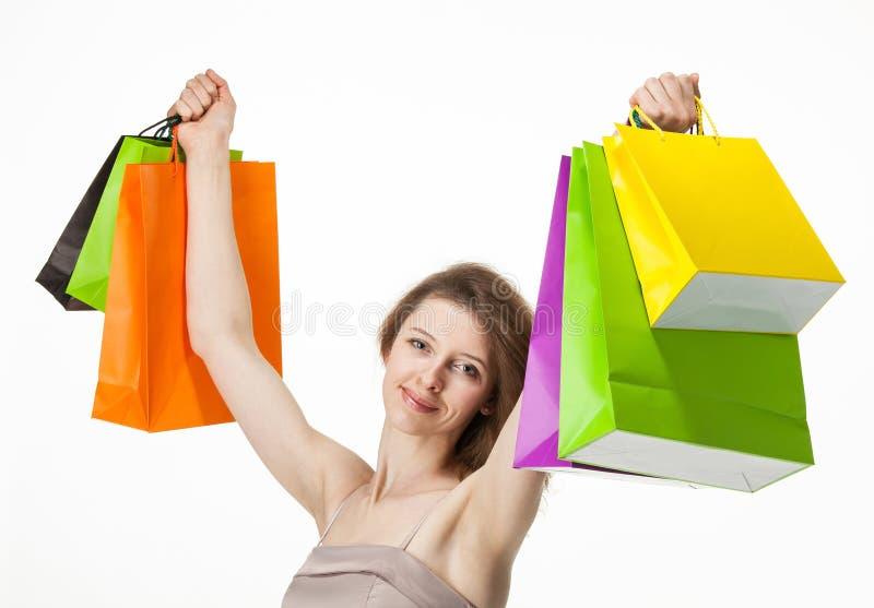 Fille attirante tenant les sacs en papier multicolores d'achats image libre de droits