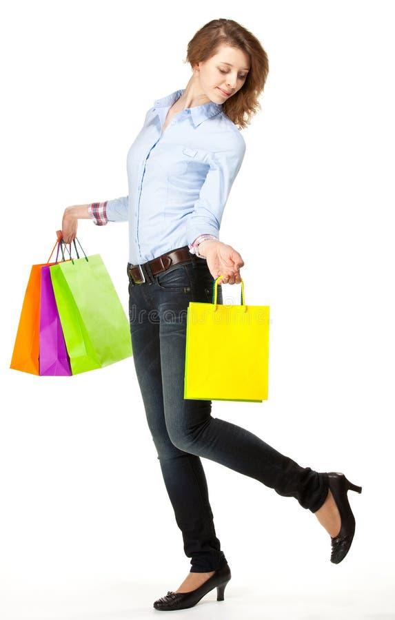 Fille attirante tenant les sacs en papier multicolores d'achats photographie stock libre de droits