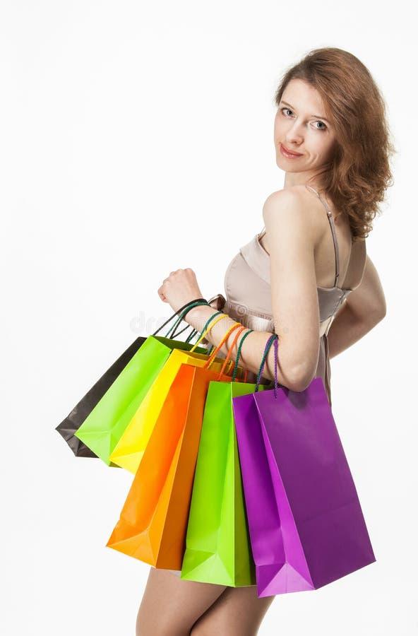 Fille attirante tenant les sacs en papier multicolores d'achats images stock