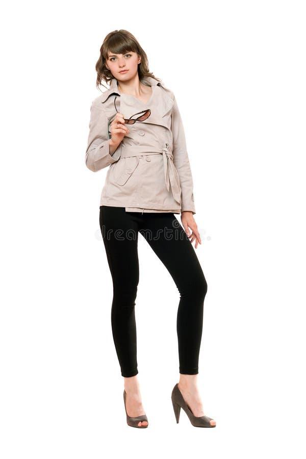 Fille attirante utilisant un manteau et des guêtres noires D'isolement photos libres de droits