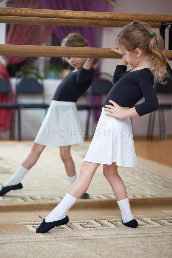 Fille au barre de ballet. Pas de ballet. Profil gauche. photo libre de droits