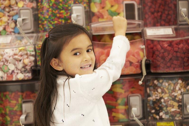 Fille au compteur de sucrerie dans le supermarché image stock