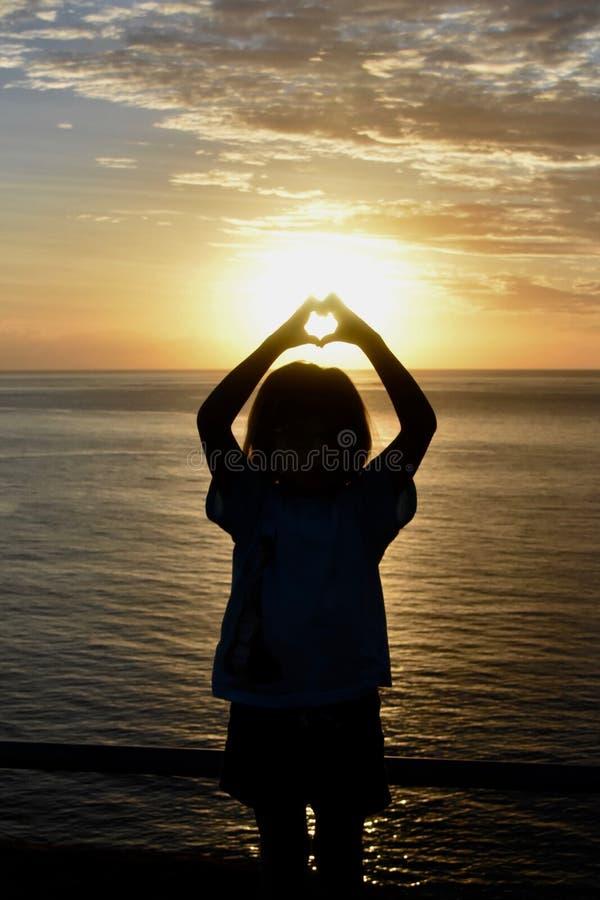 Fille au coucher du soleil dans des îles de South Pacific des Fidji faisant le coeur photo stock
