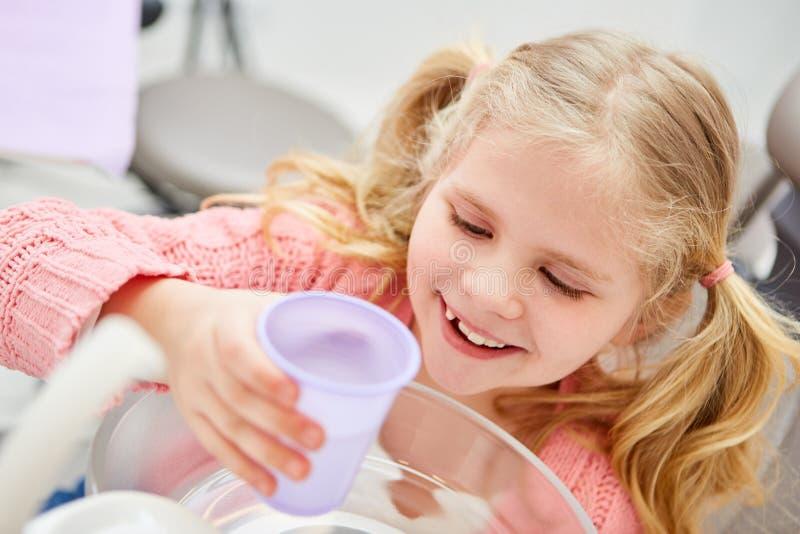 Fille au dentiste avec du verre d'eau photographie stock libre de droits