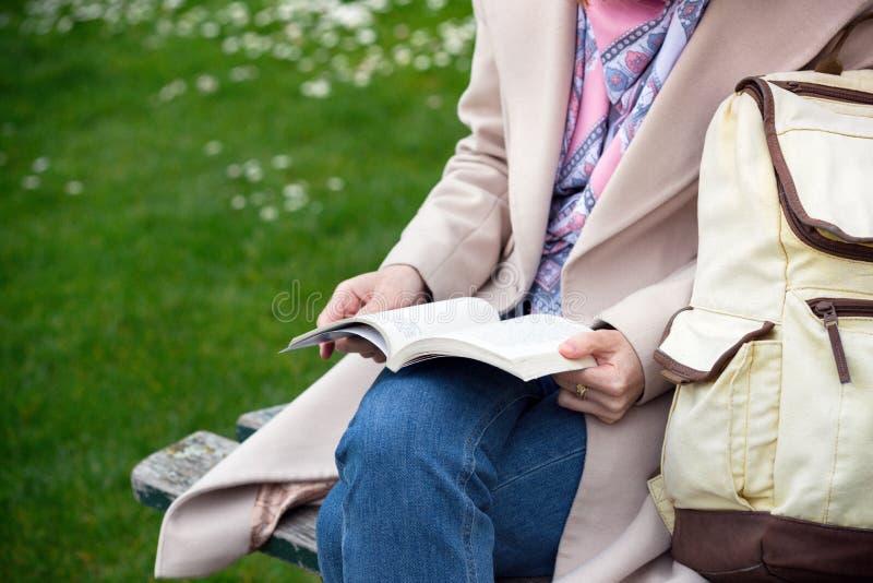 Fille au parc lisant un livre photos stock