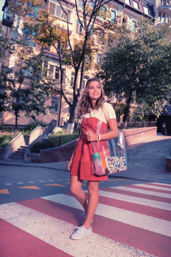 Fille aux cheveux foncés de lancement portant la robe rouge élégante traversant la rue photo stock