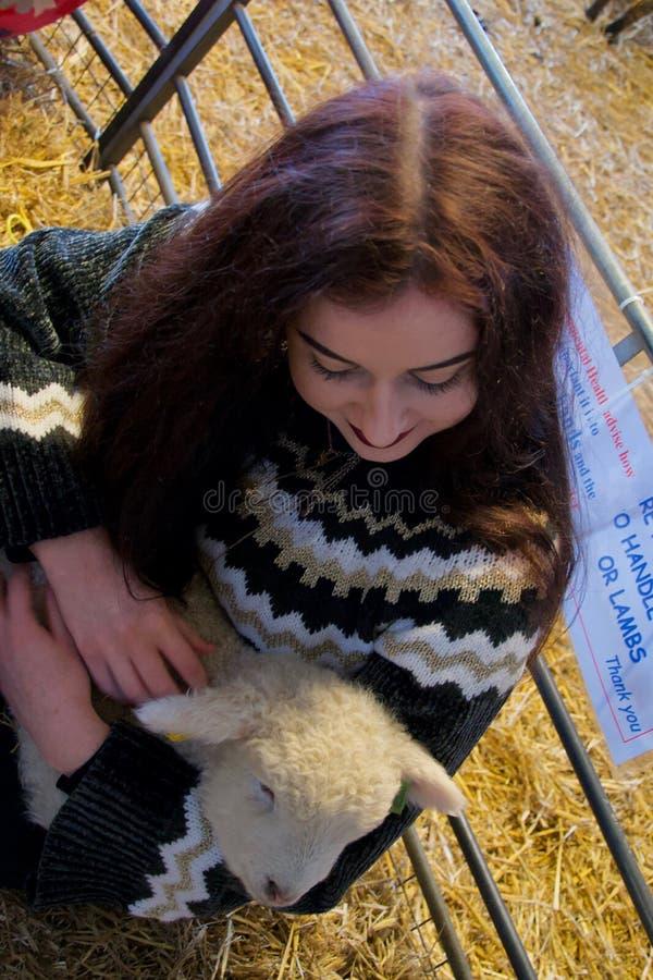Fille aux cheveux longs à une ferme étreignant un agneau nouveau-né images stock
