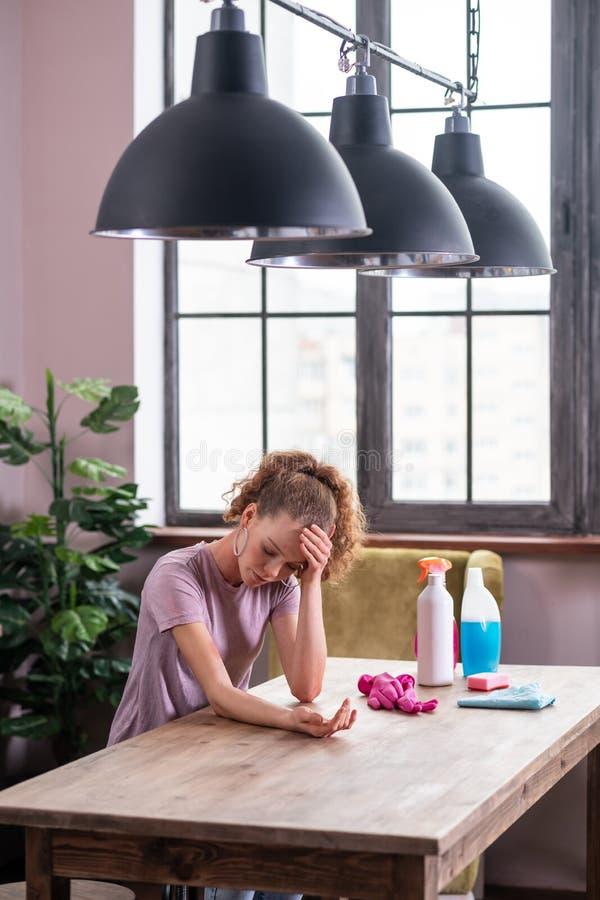 Fille aux cheveux longs déprimée se penchant sur la table et observant l'irritation image libre de droits