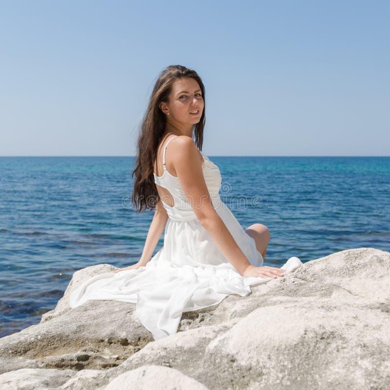 Fille aux cheveux longs dans la robe de mariage se reposant sur la pierre photo stock