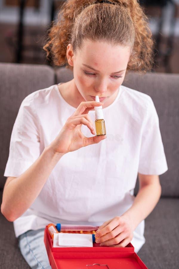 Fille aux cheveux longs inquiétée insérant la bouteille de jet dans son nez image libre de droits