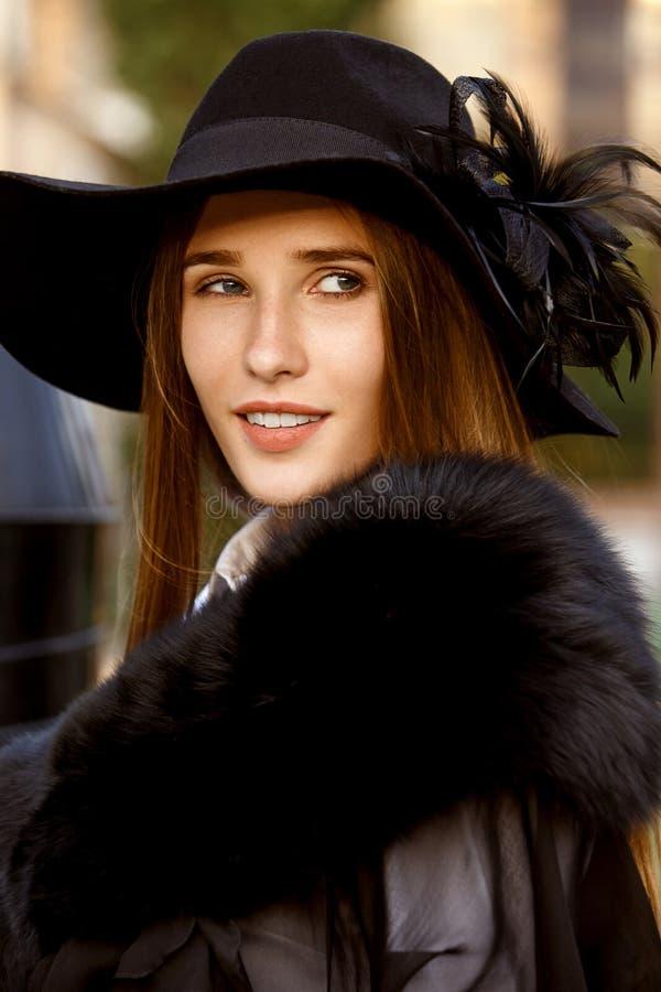 Fille aux cheveux longs mince à la mode habillée dans une veste élégante noire sur une chemise blanche, un pantalon noir et un ch photo libre de droits