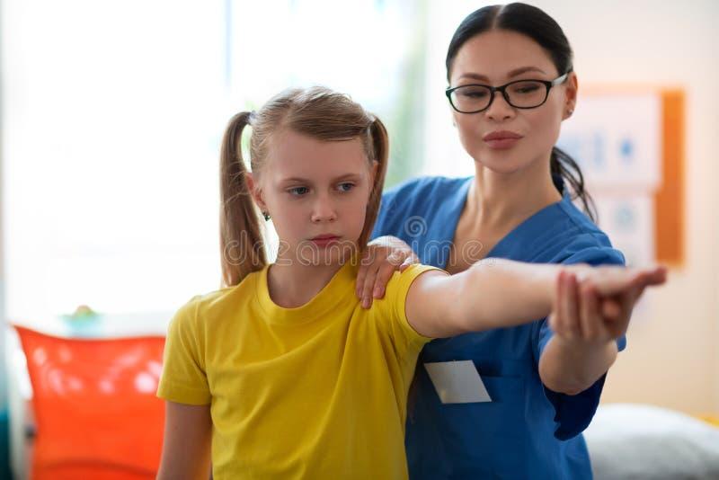 Fille aux cheveux longs sérieuse tirant la main et montrant dedans au docteur curieux photos stock