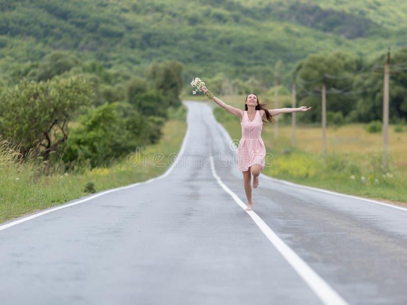 Fille aux pieds nus avec le bouquet de camomille fonctionnant le long de la route après Ra photo libre de droits