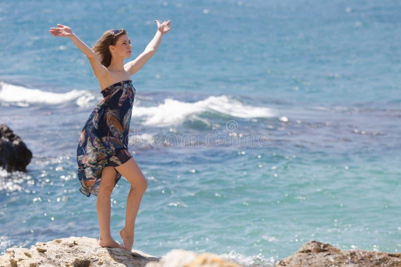 Fille aux pieds nus dans le bain de soleil posant sur la roche avec des bras augmentés photographie stock