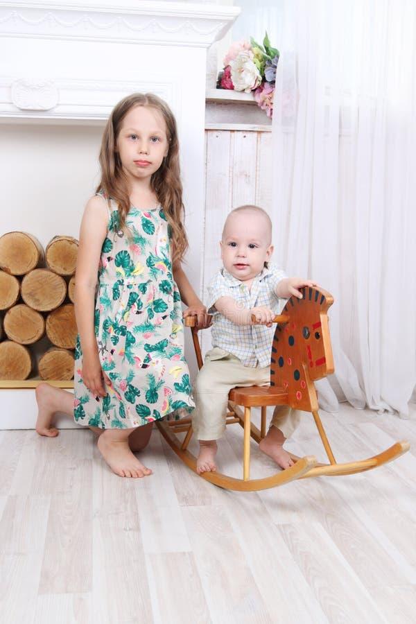 Fille aux pieds nus heureuse et son petit frère sur le cheval de basculage photos stock