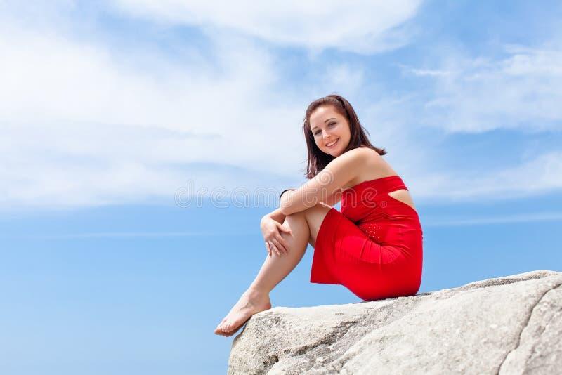 Fille aux pieds nus s'asseyant sur la roche contre le ciel image stock