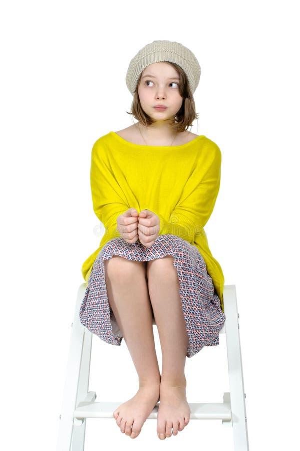 Fille aux pieds nus s'asseyant sur un escabeau avec un regard mystérieux images stock