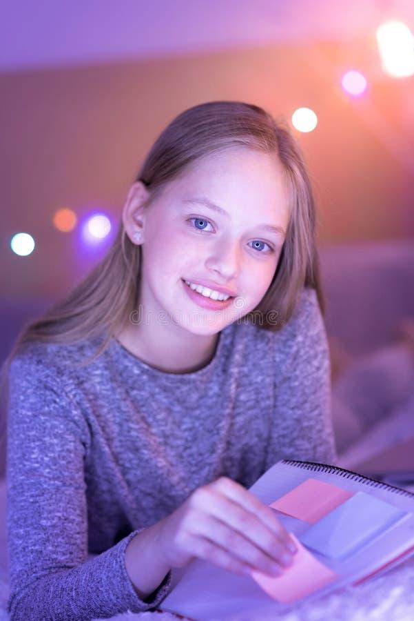 Fille aux yeux bleus souriant et tenant son carnet photographie stock libre de droits