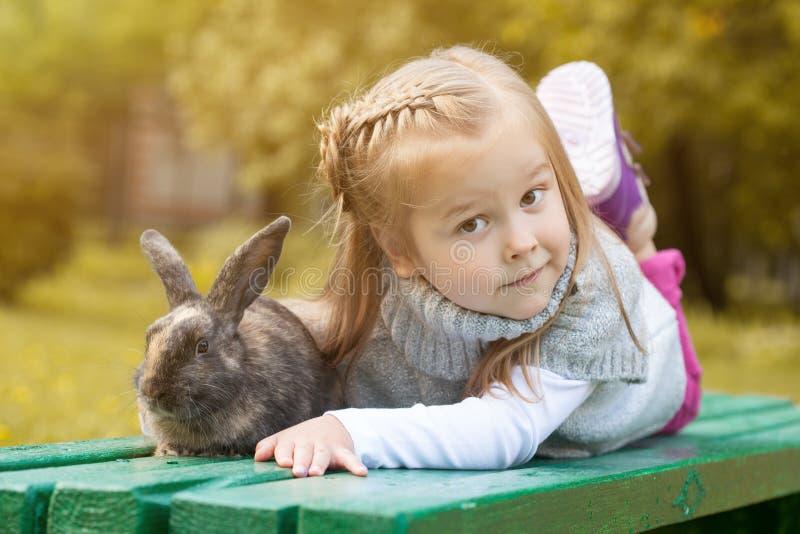 Fille aux yeux bruns mignonne se trouvant sur le banc avec le lapin photos stock