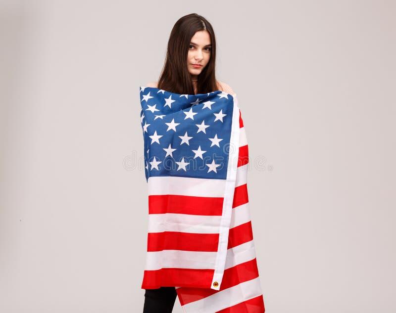 Fille avec de beaux yeux posant avec le drapeau américain sur le fond gris photographie stock libre de droits
