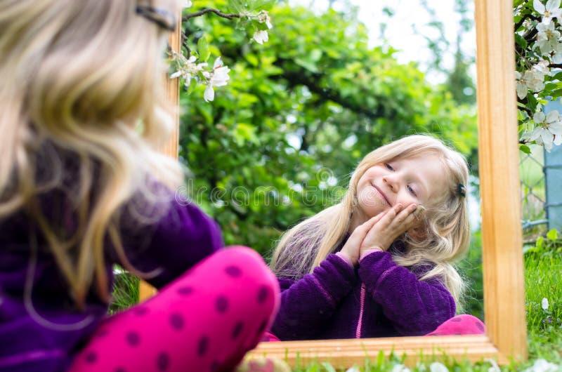Fille avec de longs cheveux blonds et miroir photo stock
