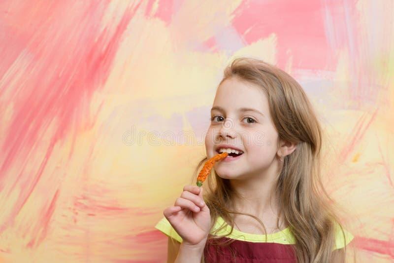 Fille avec de longs cheveux blonds mangeant du poivre frais rouge photos libres de droits