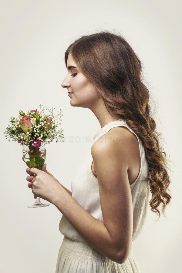 Fille avec de longs cheveux et un bouquet des fleurs dans un verre image libre de droits