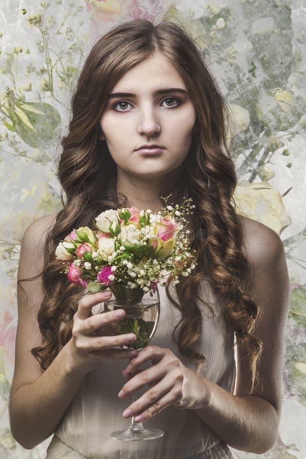 Fille avec de longs cheveux et un bouquet des fleurs dans un verre photographie stock libre de droits