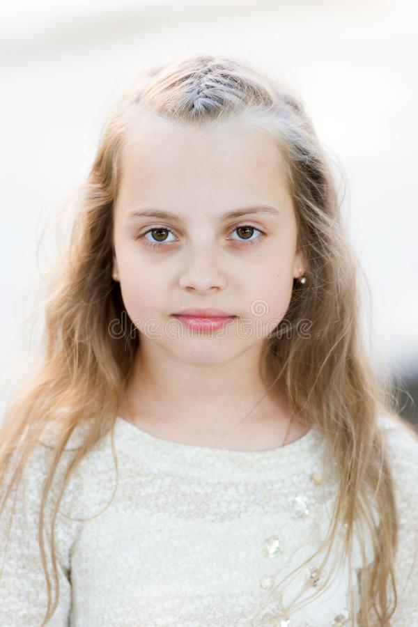 Fille avec de longs cheveux sur le visage calme, fond clair Cheveux de fille d'enfant les longs semblent mignons et tendres, fin  photographie stock libre de droits