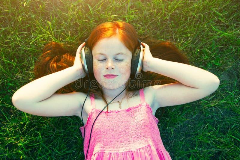 Fille avec des écouteurs écoutant la musique image stock