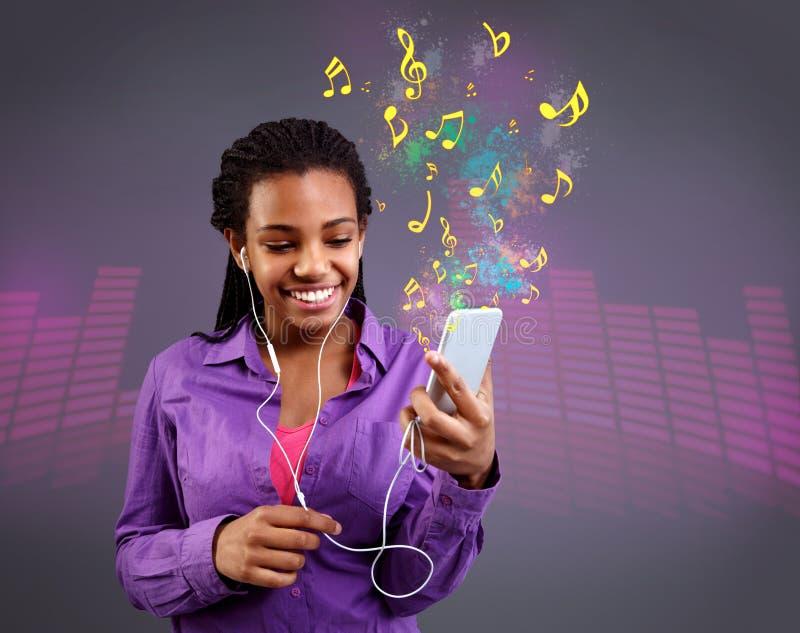 Fille avec des écouteurs écoutant la musique sur le smartphone photographie stock libre de droits
