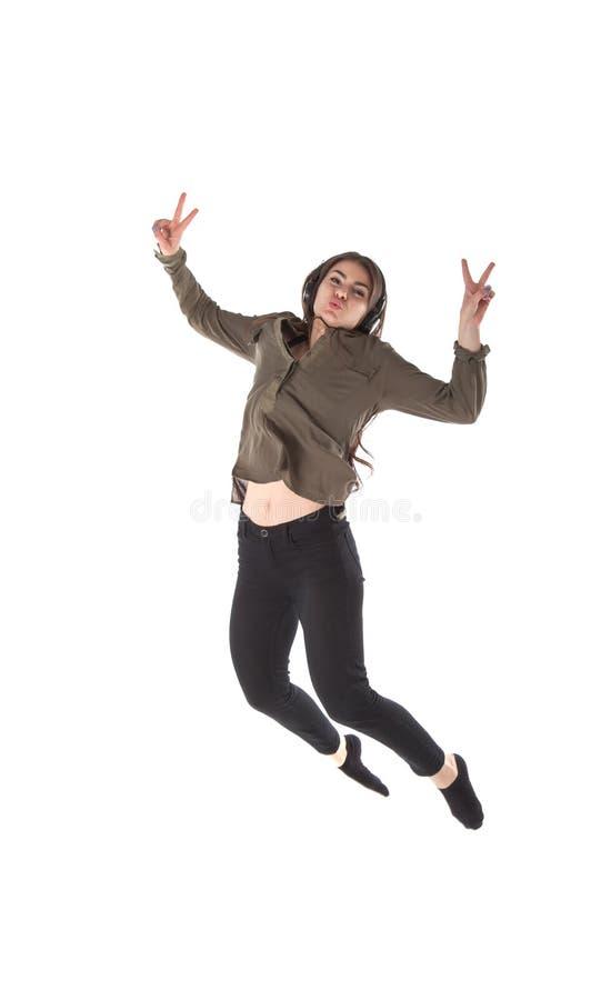 Fille avec des écouteurs qui est dansante et sautante tout en écoutant la musique photographie stock