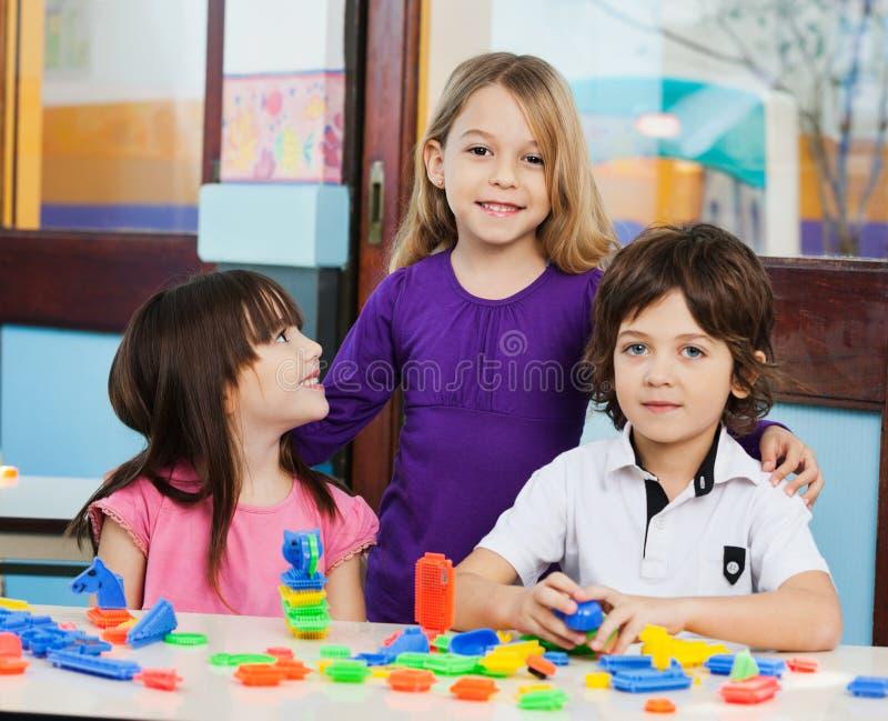 Fille avec des amis jouant des blocs dans la salle de classe photographie stock