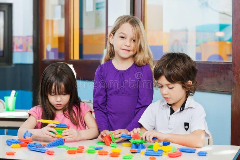 Fille avec des amis jouant des blocs dans le jardin d'enfants photographie stock libre de droits