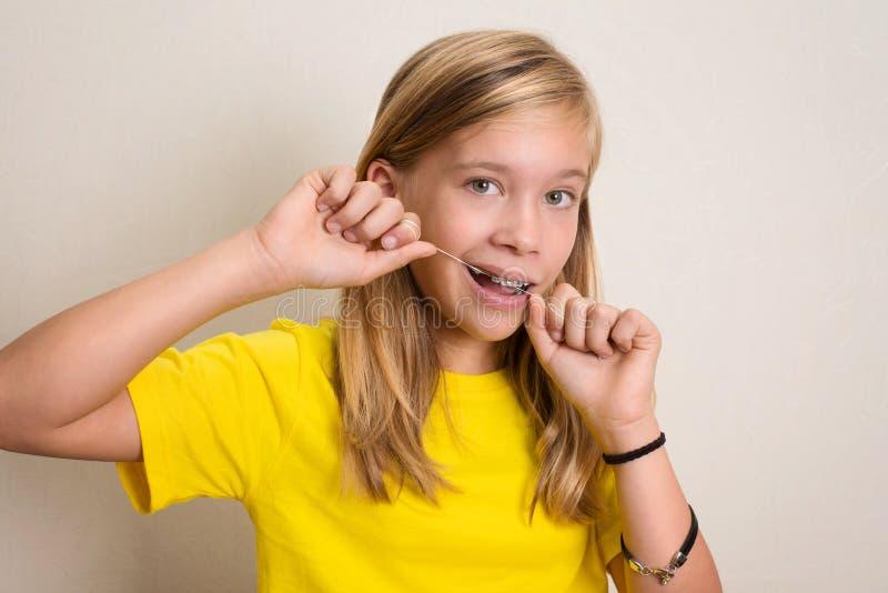 Fille avec des bagues dentaires flossing des dents Portrait en gros plan de pré photo libre de droits