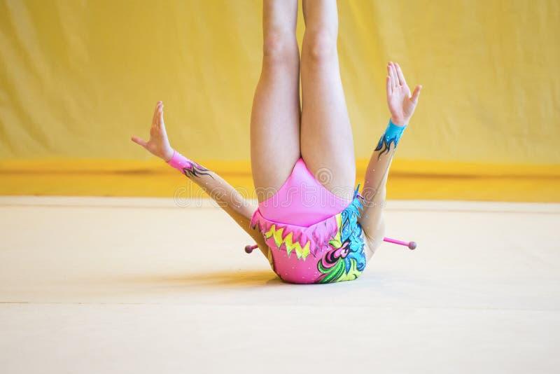 Fille avec des clubs d'une gymnastique rythmique Flexibilité dans les acrobaties image stock