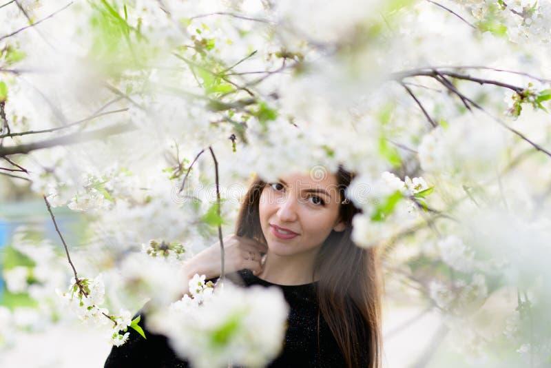 Fille avec des fleurs Jardin magnifique de modèle au printemps fille près de l'arbre au printemps Le concept du ressort jeunes de images stock