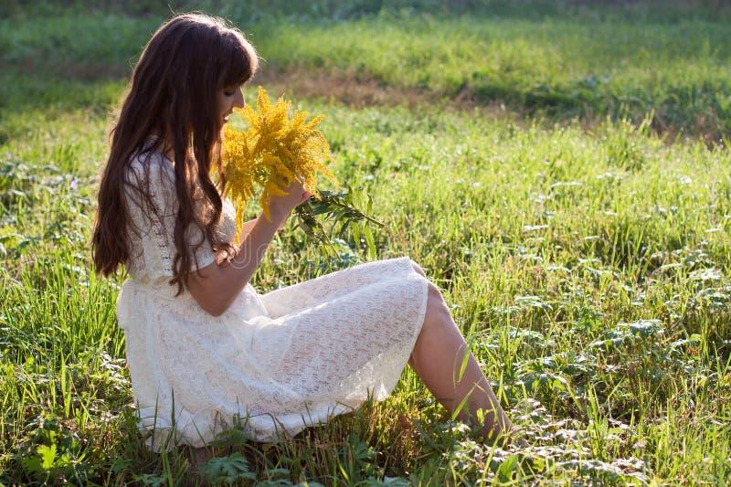 Fille avec des fleurs sur une nature de fond au printemps photographie stock