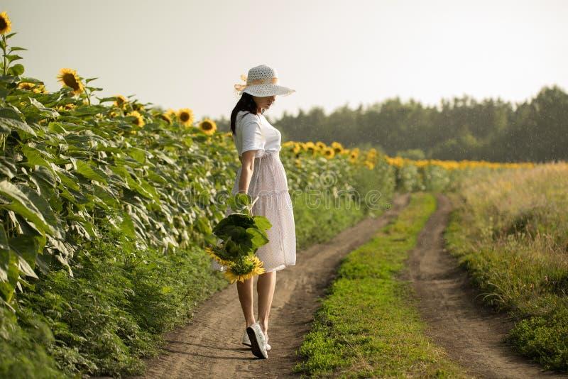 Fille avec des fleurs fille avec une position de bouquet sur le champ photographie stock libre de droits