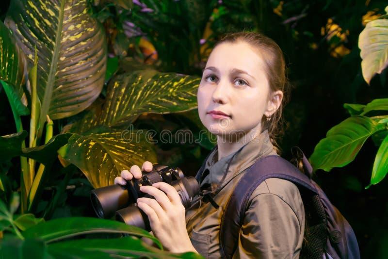 Fille avec des jumelles dans la jungle photographie stock
