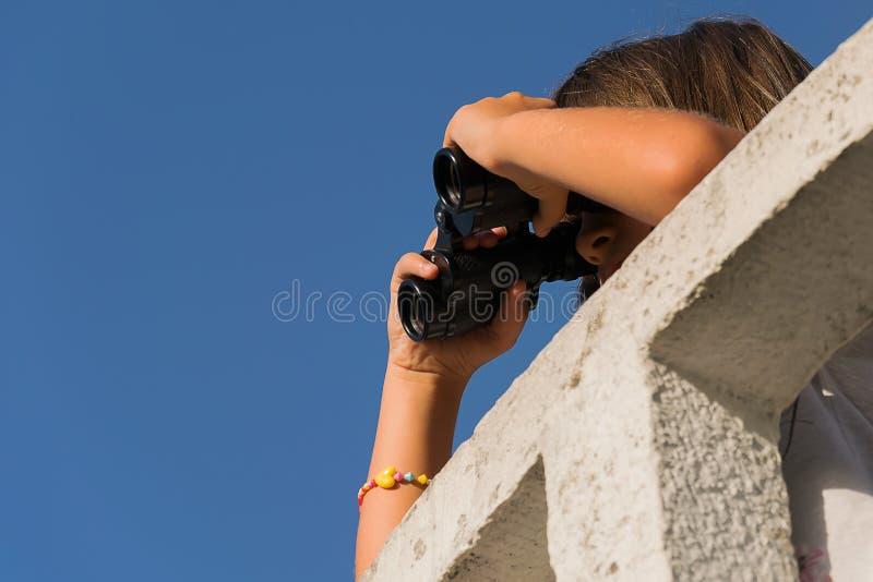 Fille avec des jumelles sur la surveillance photo libre de droits