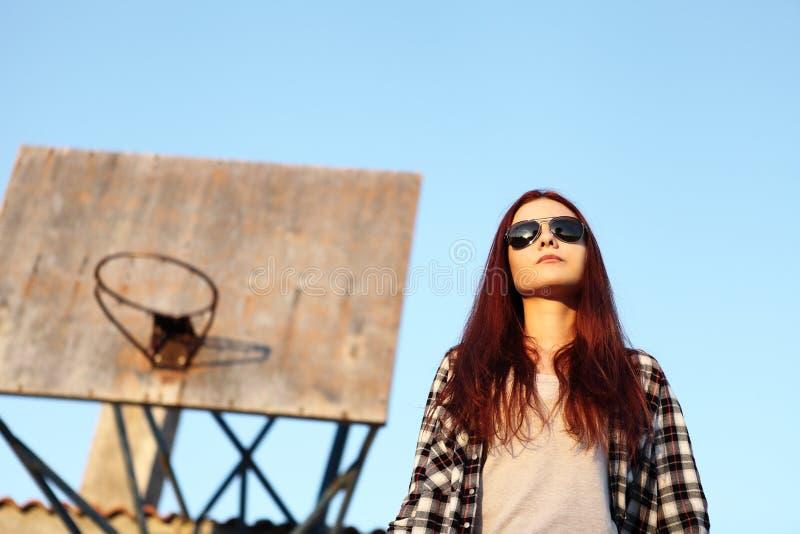Fille avec des lunettes de soleil regardant le ciel derrière le cercle de basket-ball photographie stock