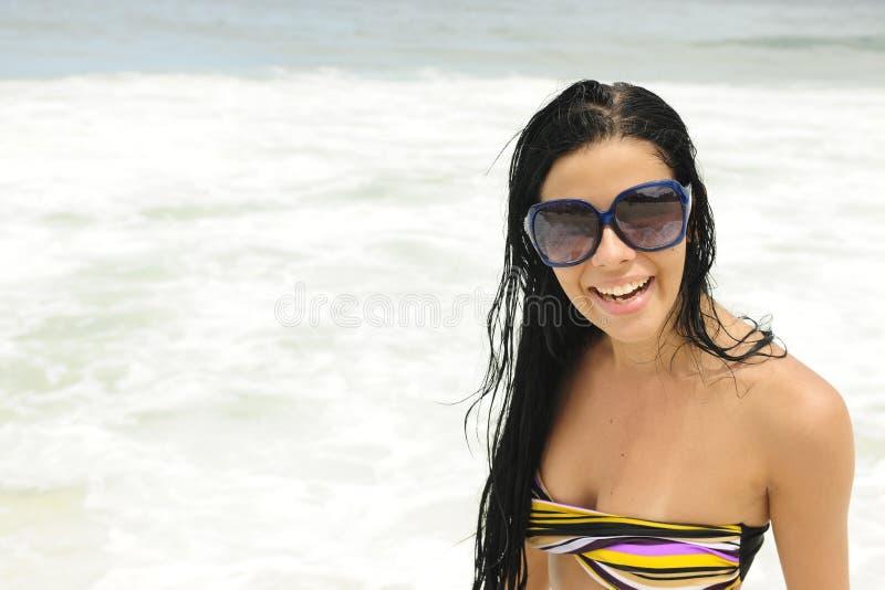 Fille avec des lunettes de soleil sur la plage photographie stock